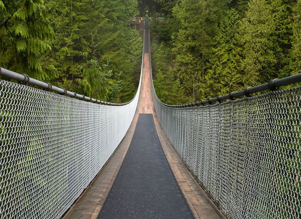A view down the length of the Capilano Suspension Bridge surrounded by lush green trees in North Vancouver, BC.