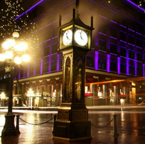 The Steamclock in Gastown stands out against a building illuminated in purple lighting in the background on a typical evening in Downtown Vancouver.