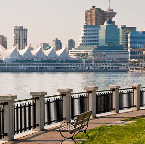 A view of Canada Place, Burrard Inlet and the downtown skyline in Vancouver, BC from behind a metal and concrete seawall with bench seating for spectators.