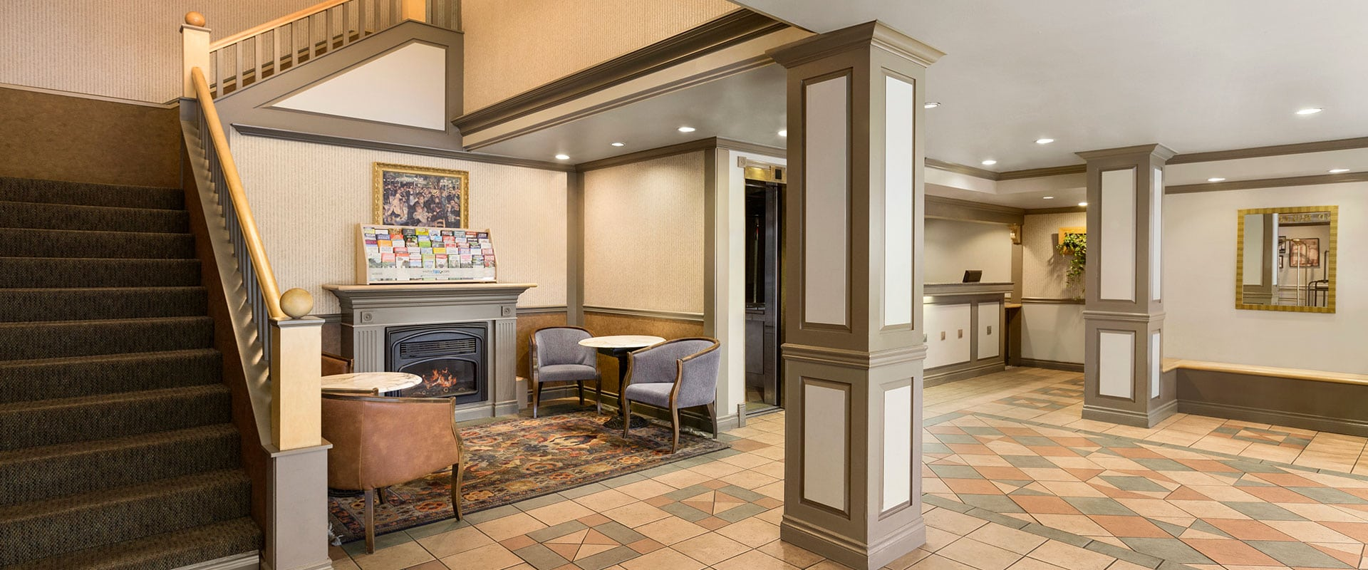 Elegant lobby at Days Inn Vancouver Downtown features a seating area with fireplace and area rug, two architectural columns and flights of stairs leading to upper floors.