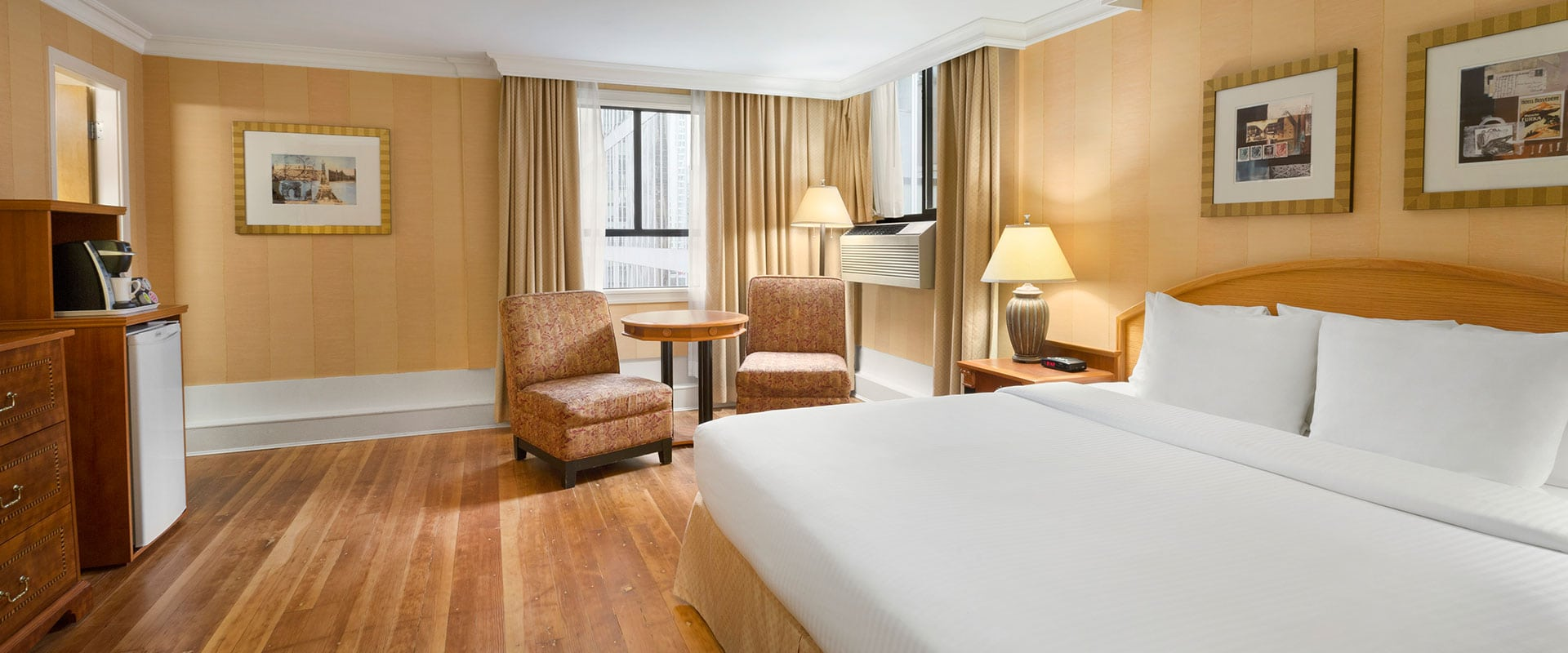 The Standard Queen suite painted in gold-yellow offers amenities such as coffee maker, mini refrigerator and air conditioner for guests at Days Inn Vancouver Downtown.