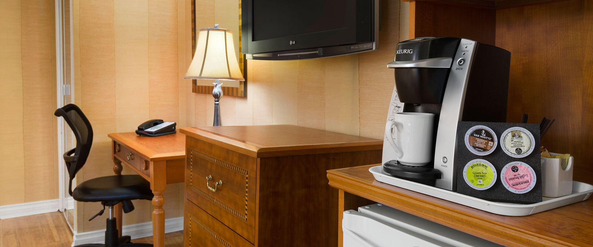 Some amenities found in a suite at Days Inn Vancouver Downtown include coffee maker, mini refrigerator, flatscreen TV and writing desk and chair.