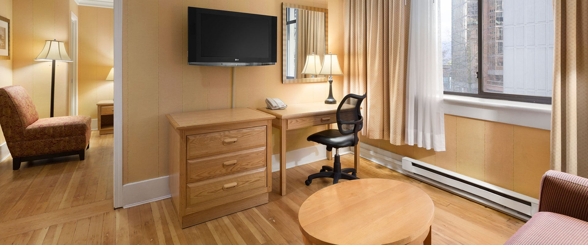 The living room of a tastefully furnished suite at Days Inn Vancouver Downtown features natural beige hardwood floors, coffee table, dresser, writing desk, and flatscreen TV.