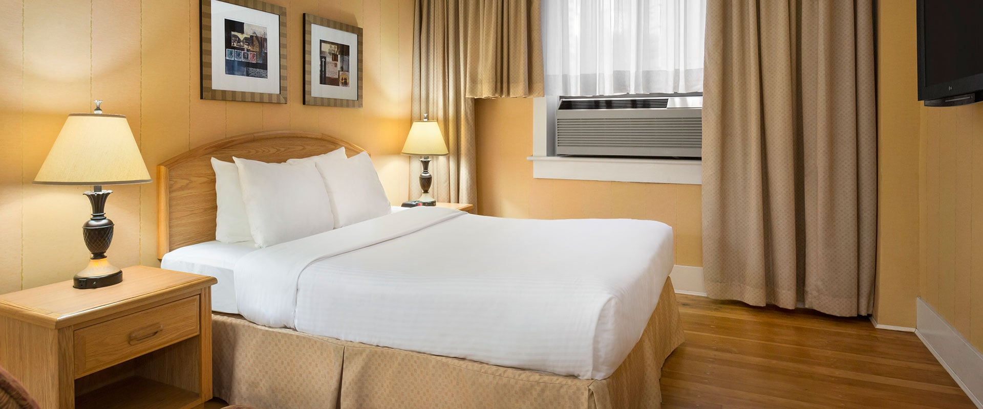 Canary yellow walls, natural wood colored bedside tables, and beige curtains are contrasted against a bed in bright white linen in the Standard Double suite at Days Inn Vancouver.