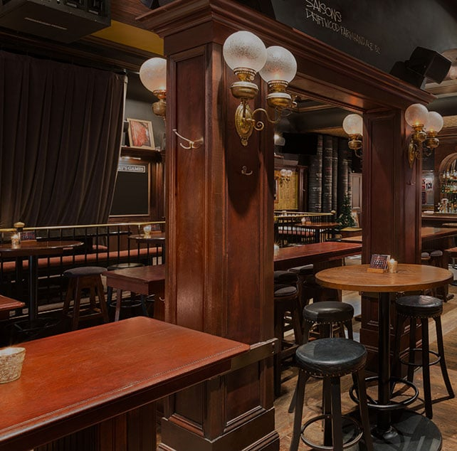 The Butcher and the Bullock pub in Vancouver Downtown has original wood flooring, rich red wood paneling, round black leather barstools and round tables.