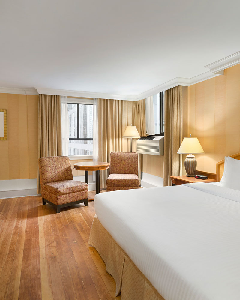 The Standard Queen suite at Days Inn Vancouver Downtown with a large bed in white linen, hard wood flooring, two patterned chairs and a round table placed by the window.