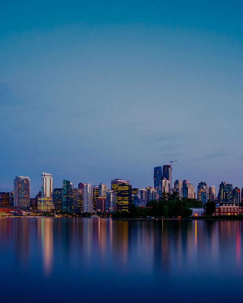 In the evening, the skyline of Downtown Vancouver reflects against the dark blue waters of Burrard Inlet.