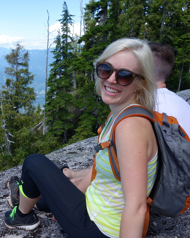 A blonde female in sunglasses and wearing a backpack, sits with a male amongst green pine trees high atop a mountain.