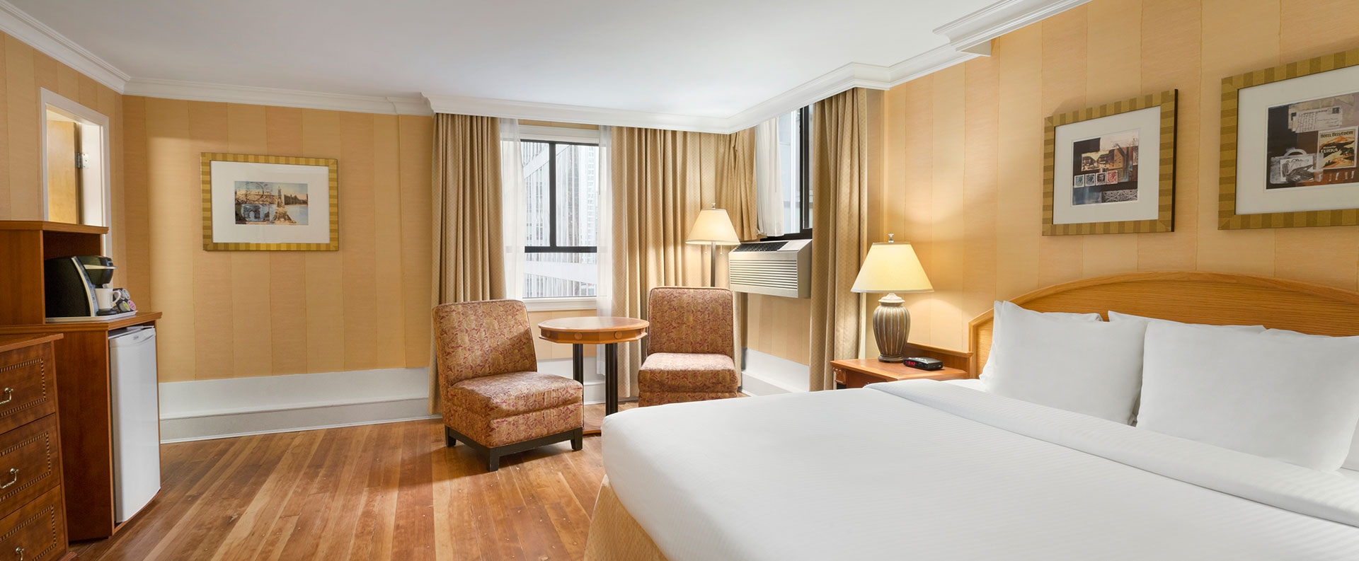 The Standard Queen room at Days Inn Vancouver Downtown features hardwood floors, comfortable chairs and tables arranged in a sitting area by the window and an air conditioner.