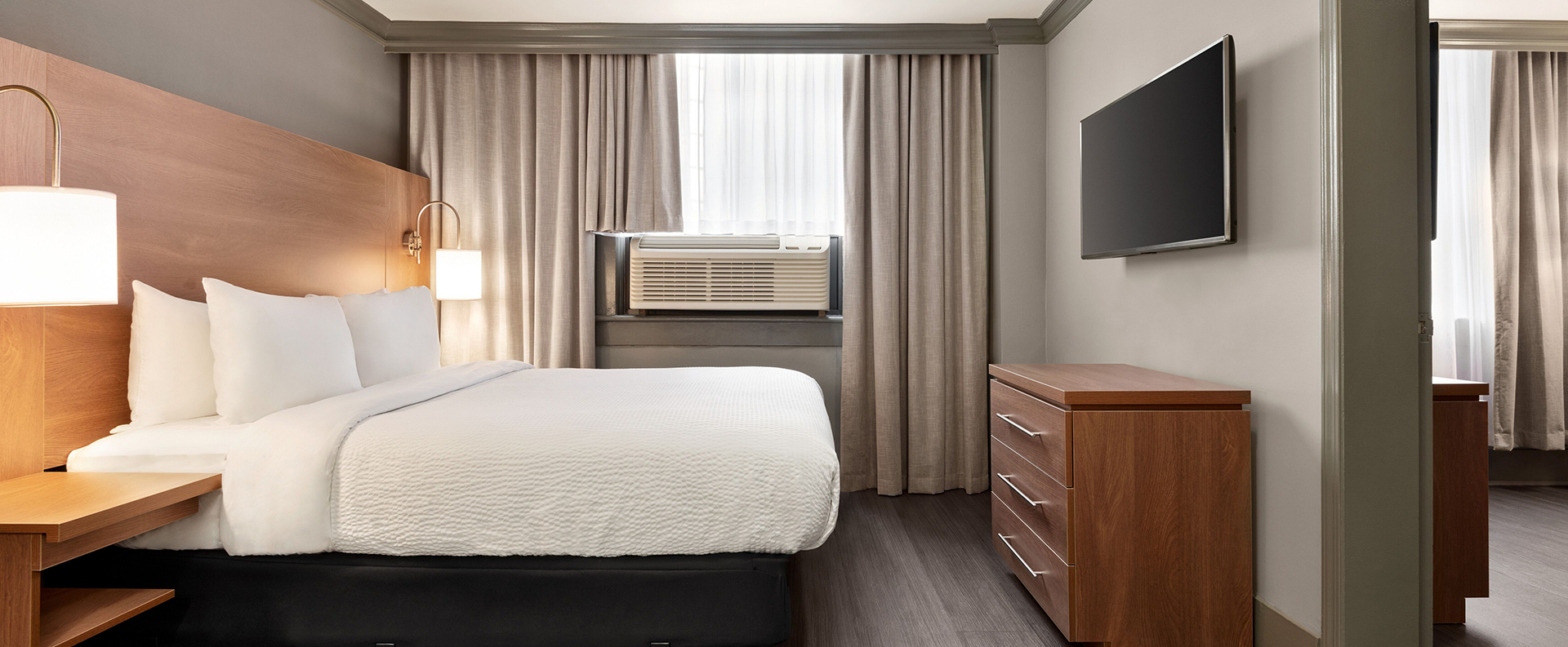 The Standard Double suite at Days Inn Vancouver Downtown with a bed made up in white linen with lamps on night tables flanking both sides of the bed.