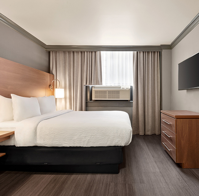 Two framed pictures hang above a bed in the Standard Queen suite at Days Inn Vancouver furnished with a bedside table and a round wood-topped table and two chairs placed by a window.