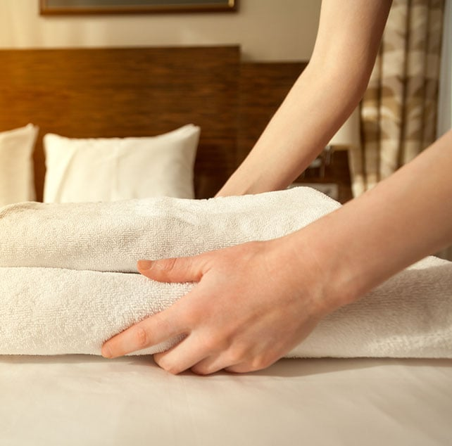 A guest services provider is laying carefully folded linen onto a bed at Days Inn Vancouver Downtown.