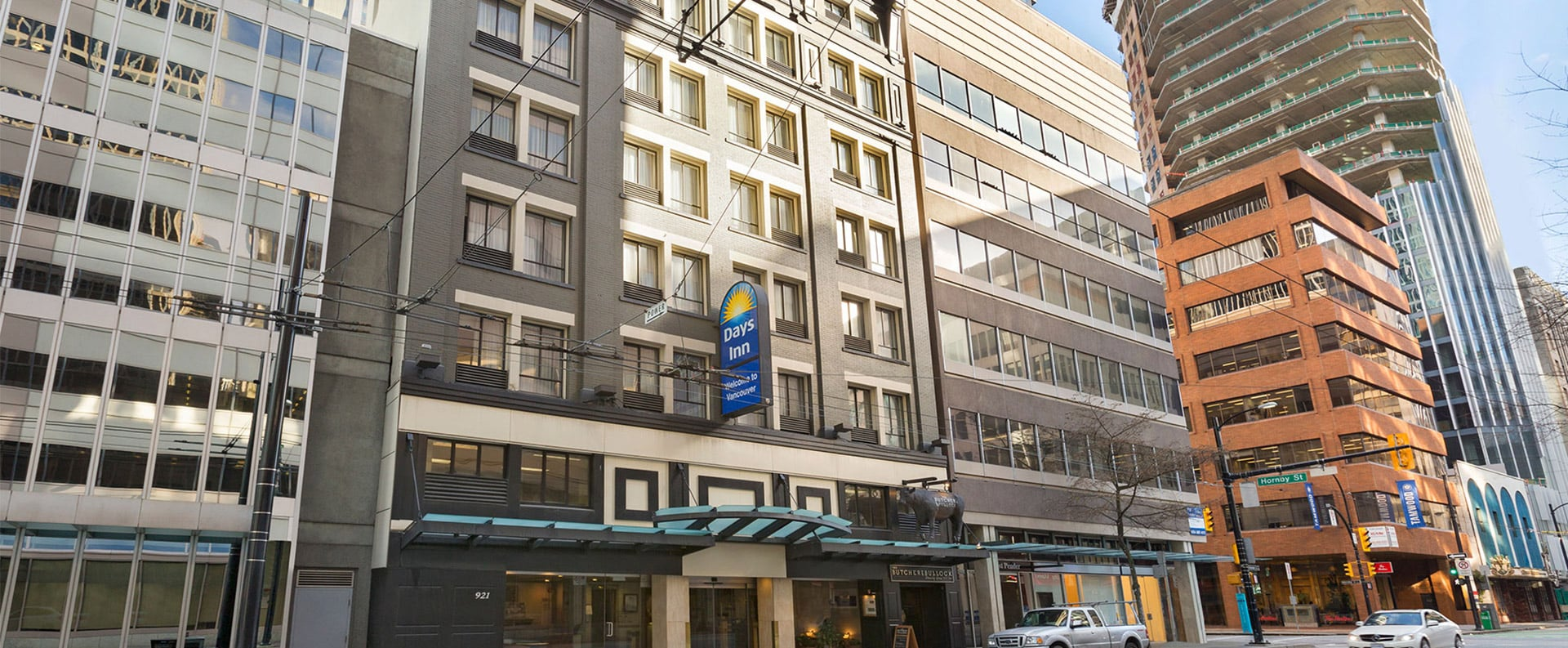 A large view of the front glass door entrance to Days Inn Vancouver Downtown with rows of windows of the hotel facing onto West Pender Street.