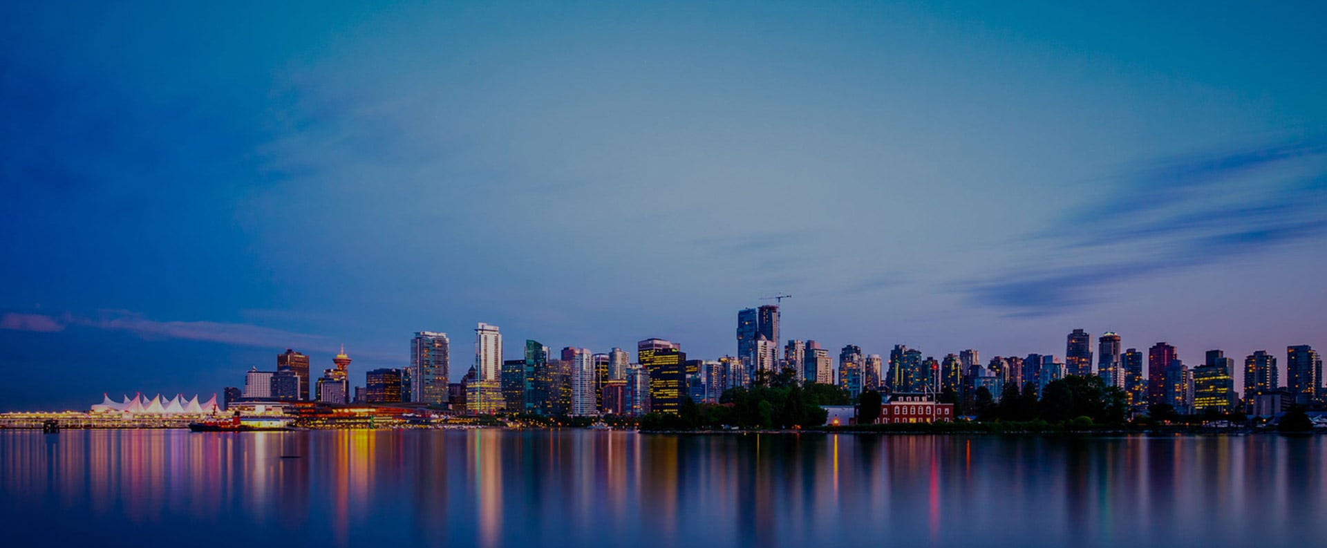 A large view of the Burrard Inlet waterfront at evening with lights from the skyline of Downtown Vancouver reflected on the waters.