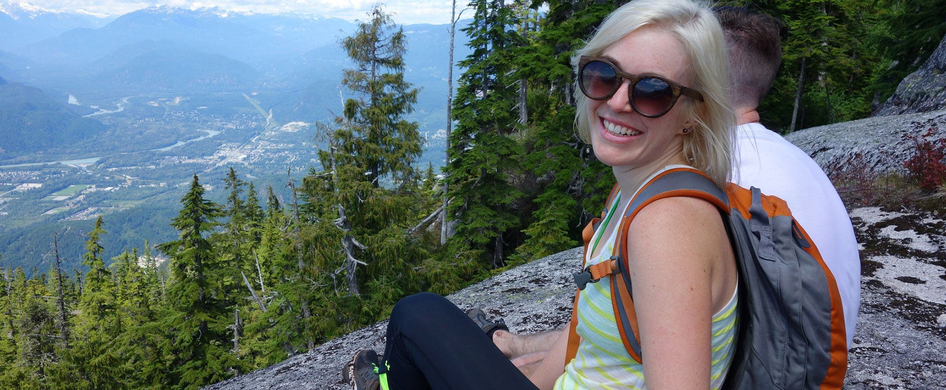 A smiling blonde female hiker in sunglasses sits on a mountain peak surrounded by green trees overlooking grasslands, green hills and mountain vegetation below.